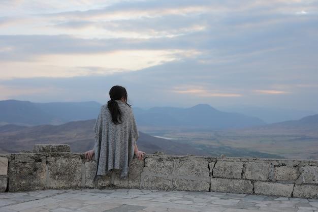 Vista posteriore di una giovane donna che ammira la bellezza delle montagne del karabakh