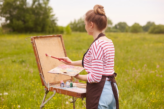Back view of young woman artist standing in front of sketchbook with brush and palette of colours