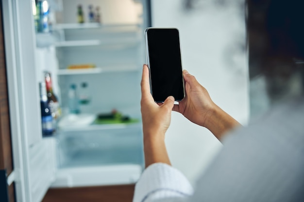 Back view of a young woman in a bathrobe holding her smartphone with both hands