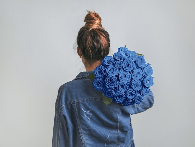 Back view of young woman in denim jacket holding bunch of classic blue roses on shoulder.