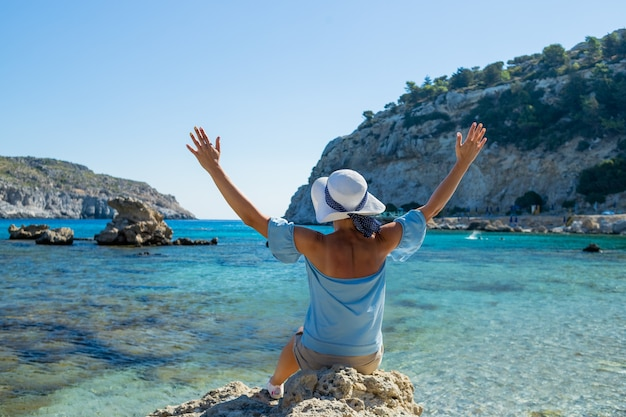 Back view of  young woman extending arms and looking forward into lagoon. woman in hat is blue bluse and white hat, relaxes on the beach