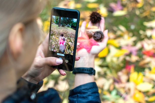 Back view of a young woman holding autumn orange maple leaves and cones on her hand and taking pictures of them on a smartphone camera in a city park.