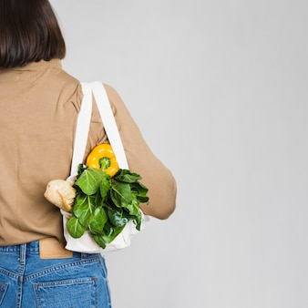 Back view young woman holding groceries bag