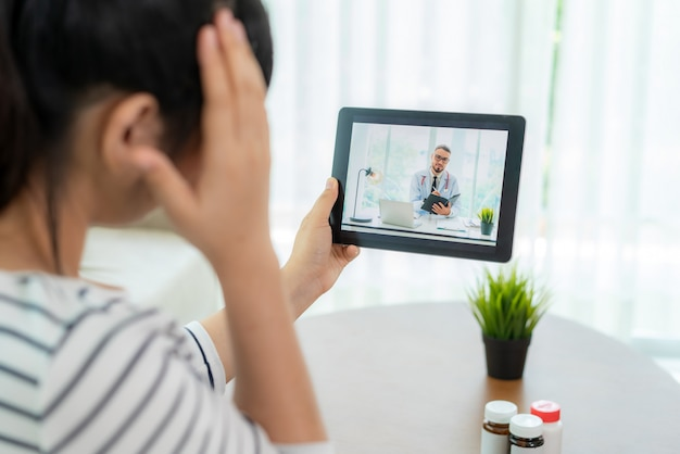 Back view of young woman making video call with her doctor with her feeling headache on digital tablet online healthcare digital technology service consultation while staying at home.