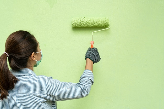 Back view of young woman painter in shirt and gloves painting a wall with paint roller.