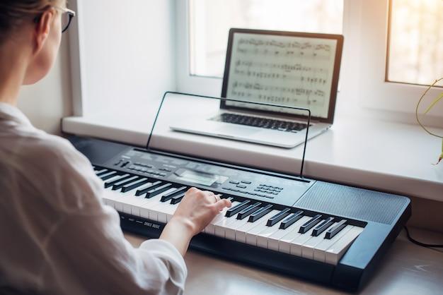 Вид сзади молодая женщина играет на синтезаторе, читая заметки на экране ноутбука, крупным планом. самостоятельное обучение игре на фортепиано в домашних условиях. увлечение музыкой, хобби, отдых, саморазвитие.