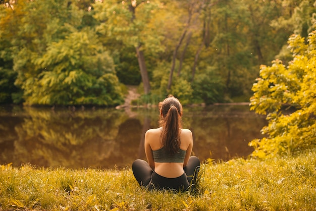 Back view of a young woman relaxing after some sport in the park near a lake.