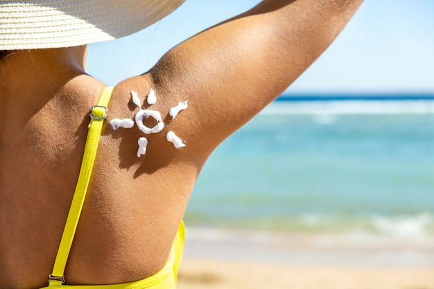 Back view of young woman tanning at the beach with sunscreen cream in sun shape on her shoulder.