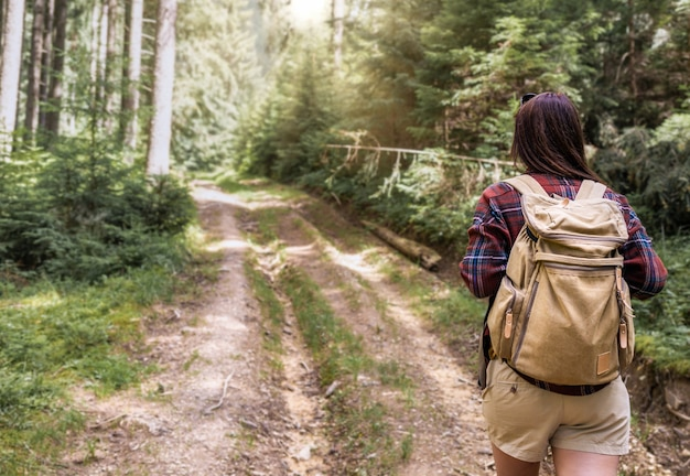 Back view young woman walks with backpacker in the forest travel and summer vacations outdoor lifestyle concept