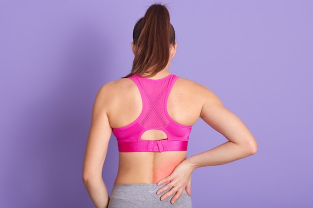 Back view of young woman with back pain standing against purple wall in studio