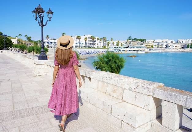 Back view of young woman with hat and dress walks towards the promenade of otranto, apulia, italy