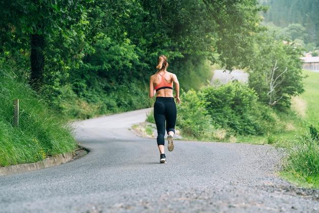 Back viewof beautiful women running across a road through a forest