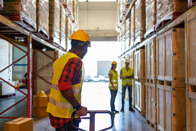 공장 창고에서 일하는 흑인 남성 노동자 팀의 뒷모습. 상품이 있는 배경 선반에 건물의 실내 팔레트 트럭을 당기는 흑인 노동자입니다. 물류 산업 개념입니다.