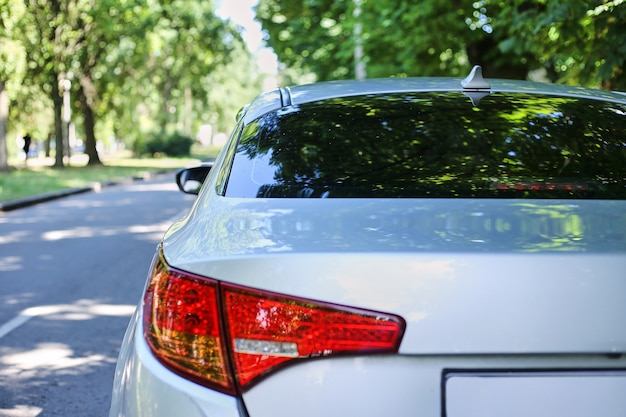 Заднее окно серого автомобиля на стоянке на улице в солнечный летний день
