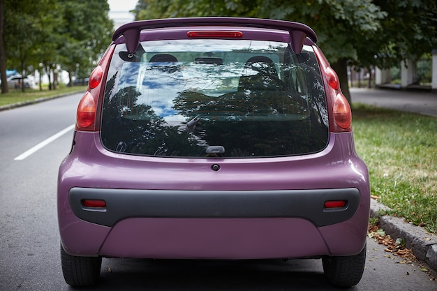 Back window of purple car parked on the street in summer sunny day, rear view. mock-up for sticker or decals