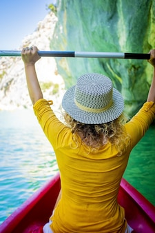 Back of woman in hat sitting on kayak holding oar with her arms raised on a beautiful lake or canyon leading towards rocky mountain coast. woman enjoying vacation kayaking on canyon water surface