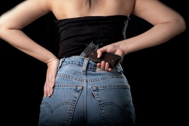 黒の表面にピストル銃を保持している女性の1つの手、拳銃を運ぶ若いセクシーな女の子、きれいな女性が銃を持って立つ