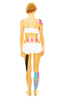 The back of woman with physio tape on different parts of her body over white background
