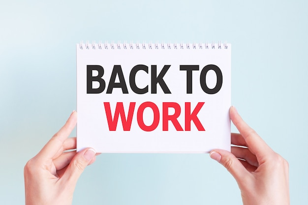 Back to work word inscription on white card paper sheet in hands of a woman