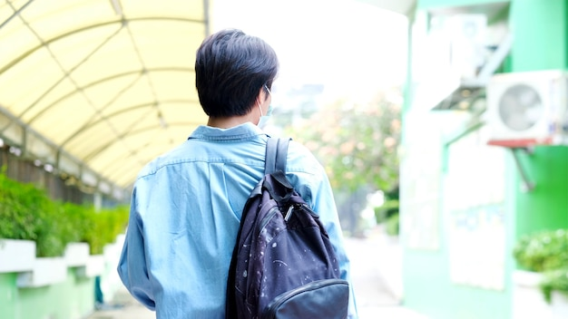 Back of young asian campus student man wearing protection mask while walking in campus