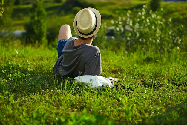 Back of young attractive modern stylish man in casual cloth in hat in glasses sitting in the park in green grass