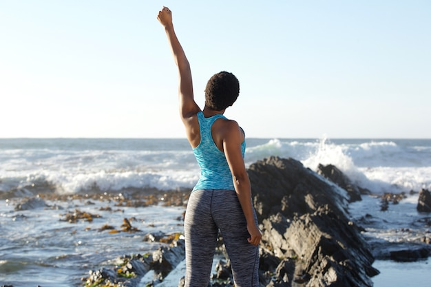 Back of young black woman looking out at sea with hand raised