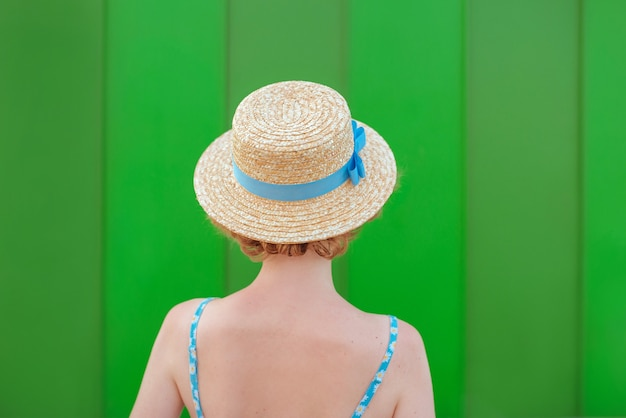 Back of young curly redhead woman in straw hat and blue sundress standing on green wall background