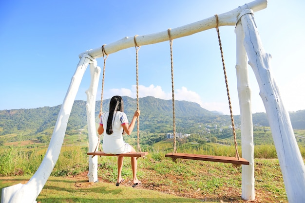 Back of young woman relaxing by swing on hillside at morning sunrise. Premium Photo
