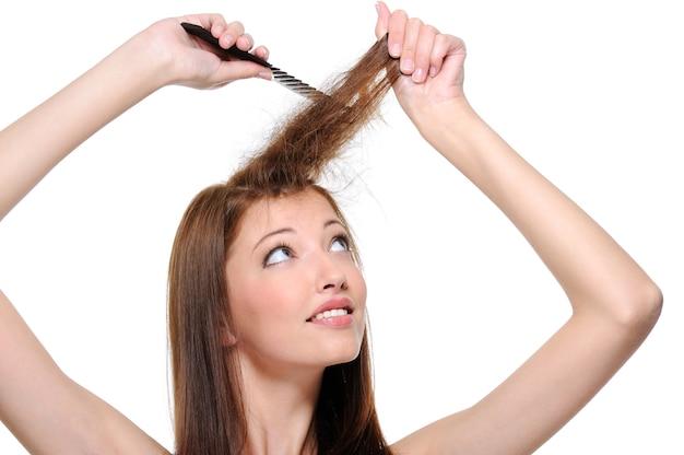 白で隔離の長いブルネットの女性の髪をバックコーミング