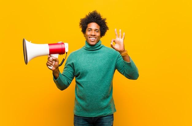 Молодой человек афроамериканца с мегафоном против оранжевого backg
