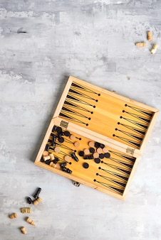Backgammon dice and pieces with a pair of chess pieces on the stone , flat lay