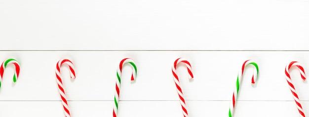 白い木製バナーbackggroundのクリスマスキャンデー杖お菓子