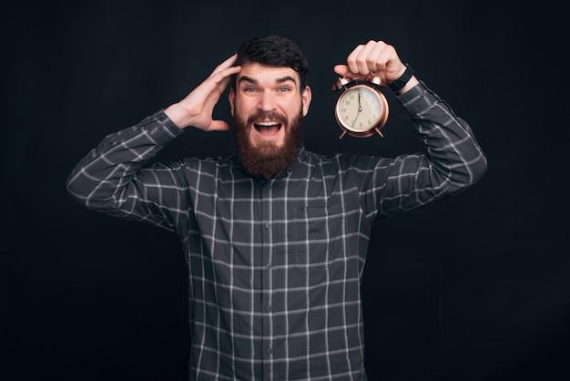 黒backgorundに目覚まし時計を保持しているひげを持つ若者
