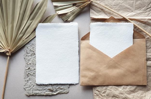 Пустой белый свадебные приглашения макеты с высушенных пальмовых листьев и конверт ремесло на текстурированной backgound таблицы. элегантный современный шаблон для фирменного стиля. тропический дизайн. плоская планировка, вид сверху