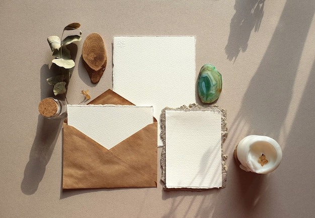 Чистые белые свадебные поздравительные открытки макеты с конвертом ремесла, высушенные листья эвкалипта на текстурированном backgound таблицы. элегантный современный шаблон для фирменного стиля. плоская планировка, вид сверху