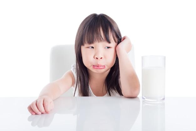 白いbackgroの上に牛乳のガラスを見て不幸な顔のアジア人少女