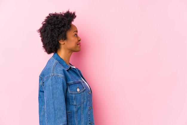 Молодая женщина против розового backgroound изолированы, глядя влево, боком поза