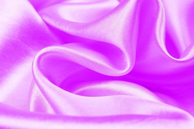 紫色のサテンの高級布のテクスチャは、結婚式の背景として使用することができます、滑らかでエレガントな紫色のシルクbackgroound
