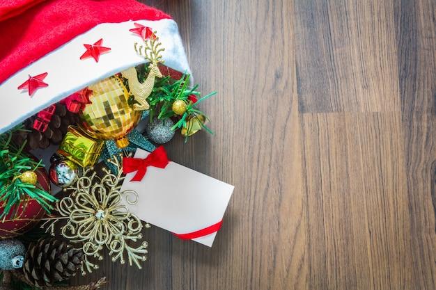 木製backgrou上の飾りとクリスマスカード、サンタの帽子