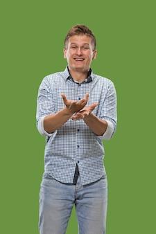 Красивый мужской поясной портрет, изолированный на зеленом backgroud студии. молодой эмоциональный удивленный человек