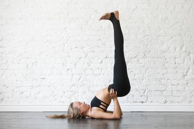 Молодая привлекательная женщина в позе випарита карани, студия backgroun