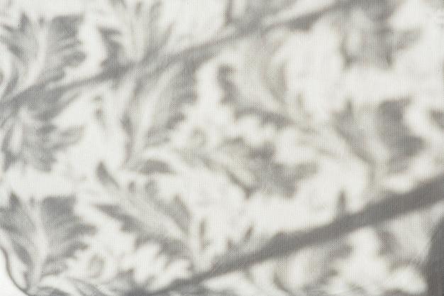 식물 그림자가 있는 회색 린넨 직물의 배경과 질감.