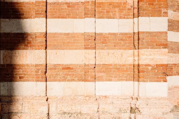 伝統的なイタリアの2色のレンガの壁の背景と質感。