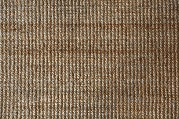Фон и текстура желтого сизаля или джутовой циновки, шерсти