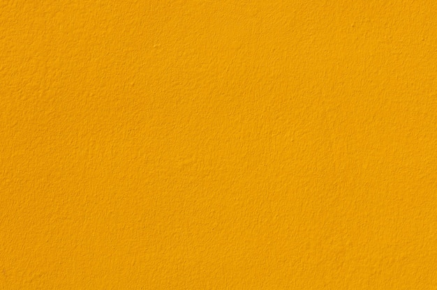 壁の漆喰に黄色のペンキ色の背景とテクスチャ。