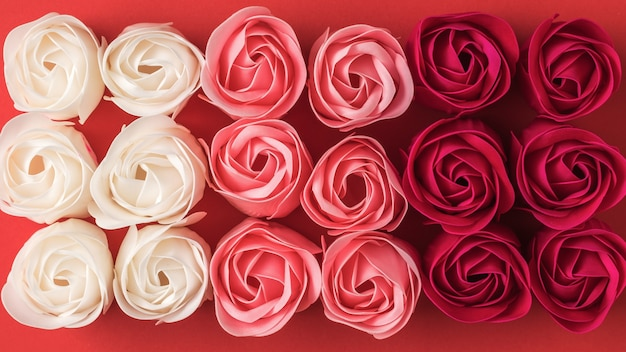 Background of artificial rose buds of three colors. floral background.