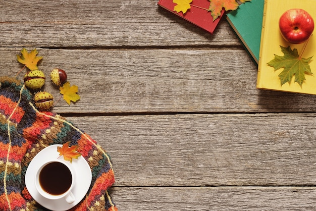Background of autumn red, green and yellow leaves, apples with cup of coffee or tea with books