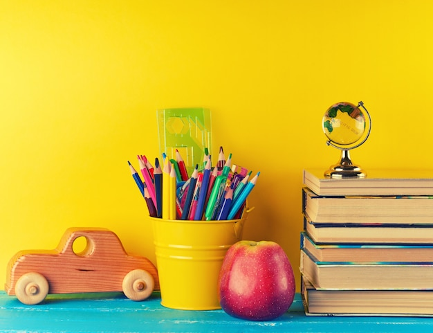Background back to school with children stationery pencils, books, apple, glass globe
