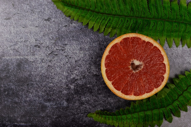 Background banner with exotic fruit grapefruit and green palm leaves on dark background
