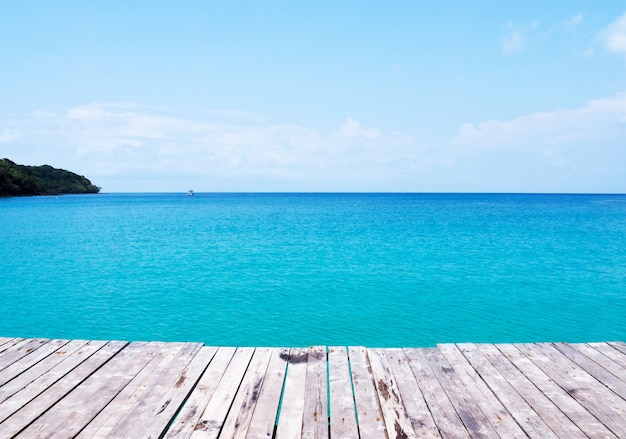 Background of beautiful nature with wooden bridge on tropical summer beach and blue sea and sky